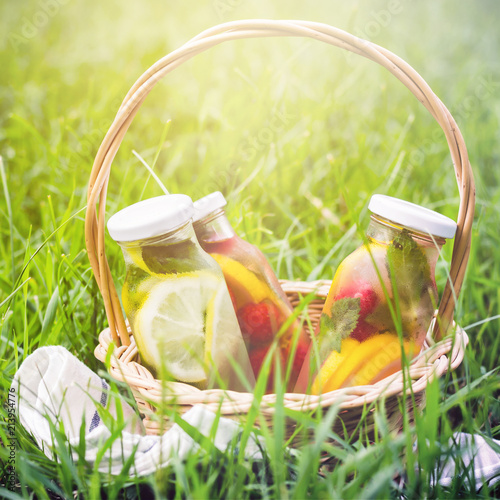 Poster Picnic Selection of summer lemonades. Basket on the meadow with refresh