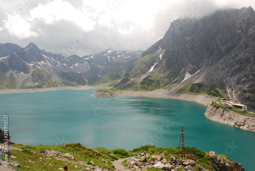 Photo Stands Salmon Scenic view of turquoise lake in snowy mountains under cloudy sky