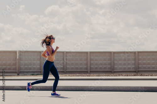 Poster Jogging Horizontal shot of sportive woman joggs in open air, enjoys sport activities, wears sport clothes, concentrated into distance, has running workout. Female runner motivates yuo to go in for sport