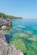 Bright clear aqua green water on Bruce Peninsula with big limestone rocks