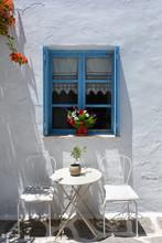 Typisch Blaues, Griechisches Fenster Mit Tisch Und Stühlen Davor Auf Den Kykladen, Griechenland