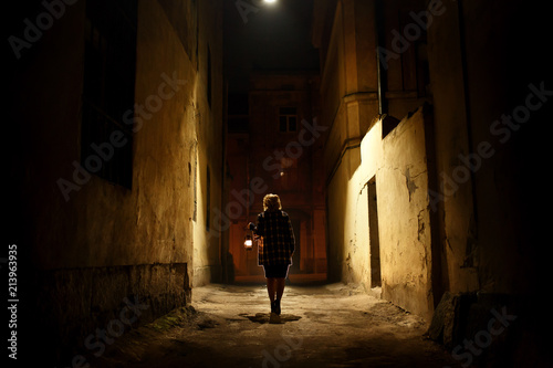 Fotografie, Obraz  Mysterious blonde woman in elegant retro coat with old oil lantern walking in ol