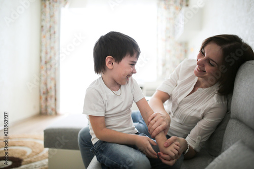 Beautiful Brunette Mom And Son Hugging Sofa