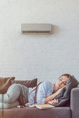 Photo  woman sleeping on sofa with book and air conditioner on wall