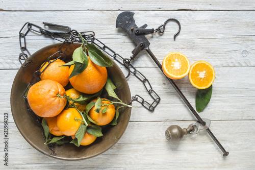 Fotografie, Obraz  agrumi arance mandarini in piatto bilancia stadera su tavolo legno grezzo bianco