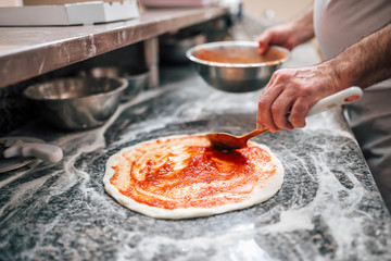 Raw pizza, preparation in traditional style. Adding tomato sauce on a pizza d...