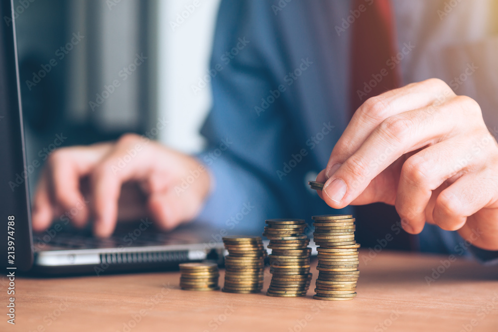 Fototapeta Finances and budgeting, businessman stacking coins