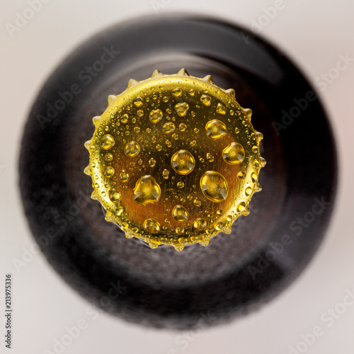In de dag Bier / Cider Bottle with soft drinks or alcohol in the ice. On gold caps and a bottle neck are drops of dew. Beer bottle cap close-up macro Isolated on white background with clipping path.