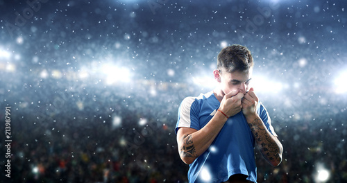 Fotografia Soccer player celebrates a victory on the professional stadium while it's snowing