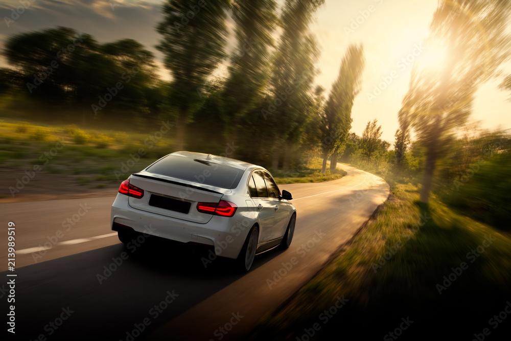 Fototapeta White car is driving on empty countryside asphalt road at sunset