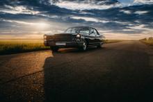 Black Retro Vintage Muscle Car Is Parked At Countryside Asphalt Road At Golden Sunset