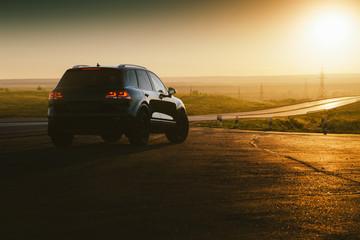 Black car is parked at countryside asphalt road near highway at golden sunset