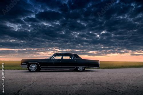 Poster Vintage voitures Black retro vintage muscle car is parked at countryside asphalt road at golden sunset