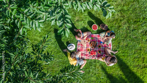 Happy family having picnic in park, parents with kids sitting on grass and eatin Fotobehang