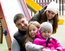 Happy Family Of Four At Children's Playground