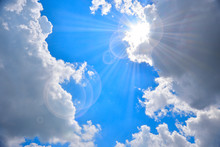 Dark Clouds With Sun Light And Flare On Blue Sky.