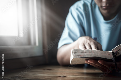 Valokuva Young man reading Holy Bible next to the window at home.