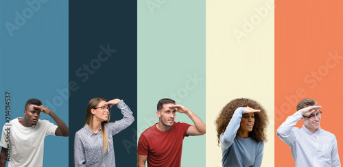 Group of people over vintage colors background very happy and smiling looking far away with hand over head. Searching concept.