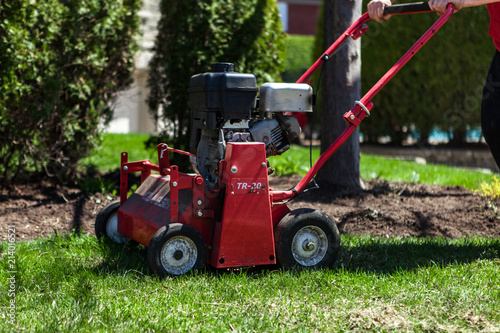 Valokuva  Red lawn aerator pictured on beautiful short green grass