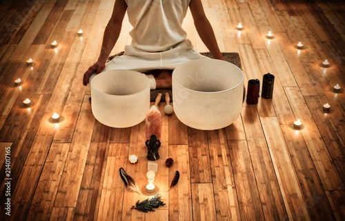 Fotografie, Obraz  Man sitting in indian behind his two musical crystal bowls, with a display of sa