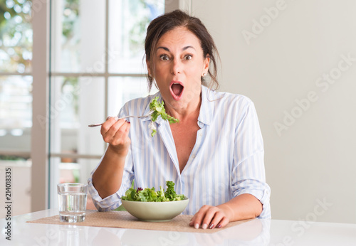 Middle aged woman eating fresh salad in a bowl at home scared in shock with a su Canvas-taulu