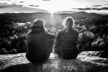 Cute Couple Sitting On The Top Of A Mountain, Facing The Sun With Flares Between Them, Seen From Behind, Black And White