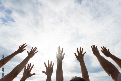 Photo Many hands raised up against the blue sky