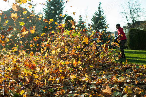 Photo Autumn leaves being blown away with man in the background