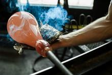 Glass-blower Man Working With Hot Ocher Glass To Make A Blown Glass Lantern