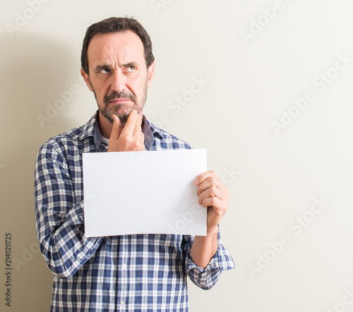 Senior man holding blank paper sheet serious face thinking about question, very confused idea
