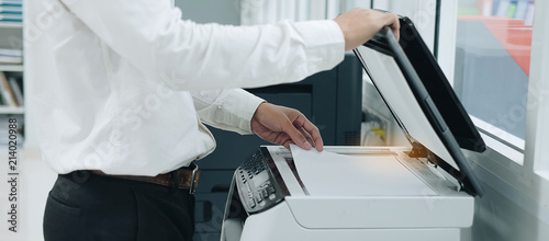 Photo Bussiness man Hand putting a document paper into printer scanner or laser copy m