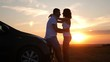 Silhouette of happiness couple stay near the new car under sky. Beautiful young couple standing near car at sunset.