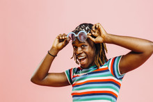 Very Happy Young Man In Striped Shirt And Big Sunglasses, Standing In Front Of A Pink Background