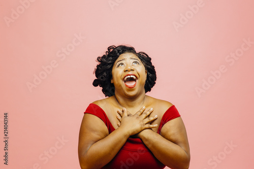 In great awe/Portrait of an extremely excited woman looking up with both hands b Fototapeta