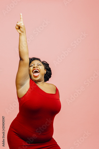 Obraz A very happy and excited woman celebrating success with arm up, mouth open and finger pointing up - fototapety do salonu