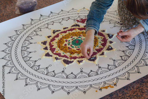 Hand of the woman creating a mandala by means of color sand