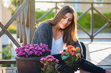 Beautiful Young Woman Gardening In Pots On The Terrace,at Home, With Working Gloves. Gardening As Hobby And Leisure Concept.