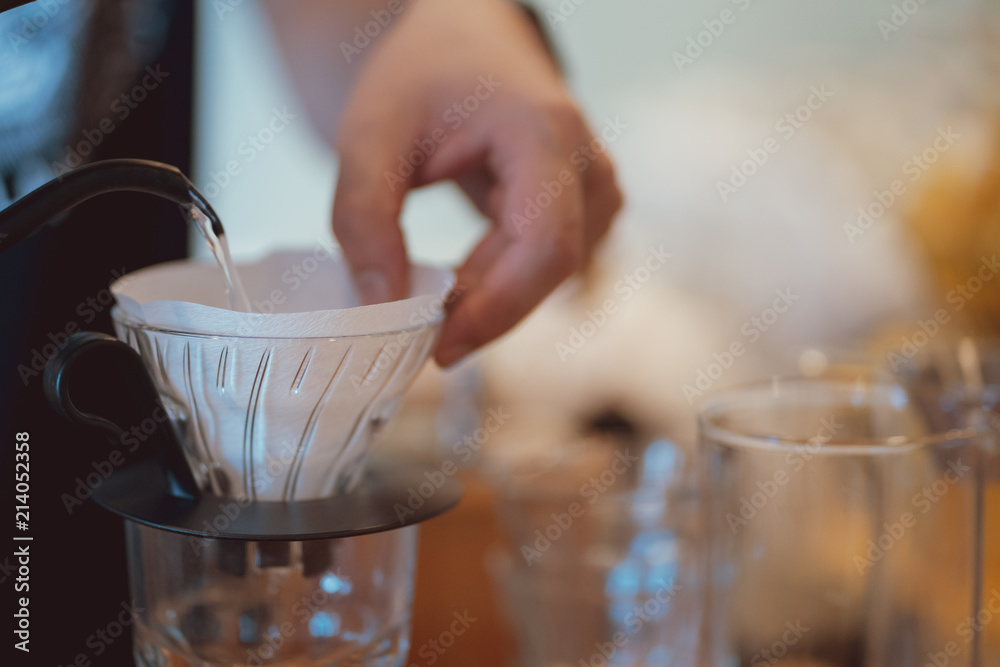 Fototapeta barista pour hot water to wet paper filter on dripper, coffee brewing process