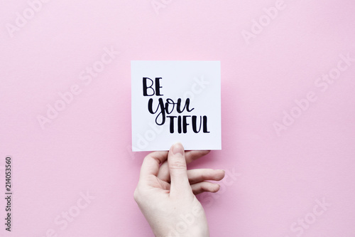 Minimal composition on a pink pastel background with girl's hand holding card wi Canvas Print