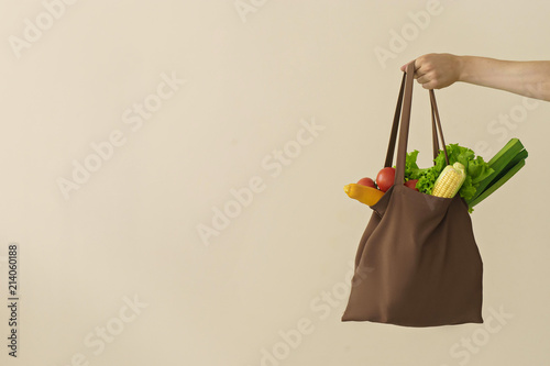 Fotografía  man hand holding cotton grocery bag with vegetables