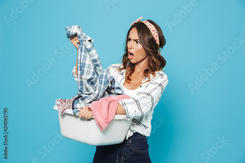 Fotografía  Photo of annoyed brunette housewife 20s carrying laundry basket with dirty cloth