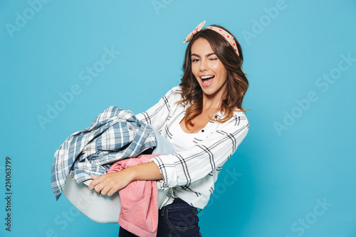 Portrait of european brunette housewife 20s carrying laundry basket with dirty o Canvas-taulu