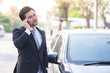 Handsome businessman using a mobile phone lerning on his car