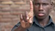 Blurred young black man showing his index finger.Stop,refuse- slow motion