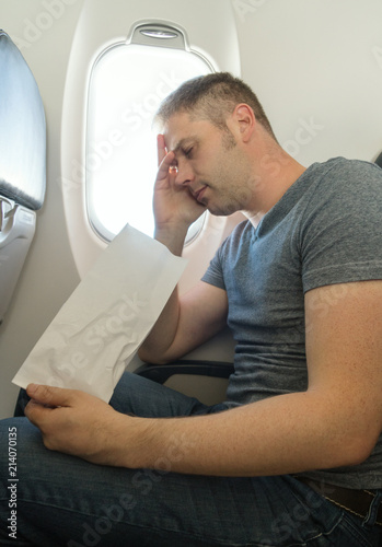 Fotografia  Airsickness. Man feels very bad on the plane.