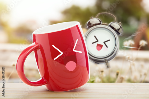 Cuadros en Lienzo Red cup of coffee and alarm clock with a happy smile on wooden table against natural background in the morning