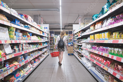 Back of a stylish woman walking in a supermarket with a basket in their hands and buying products. Shopping in a supermarket. Girl walks a supermarket and chooses shopping