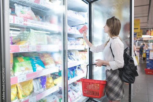 Obraz Stylish woman buys frozen food at a supermarket. Attractive young woman stands beside a freezer and chooses frozen foods. Purchase of products in a supermarket. - fototapety do salonu