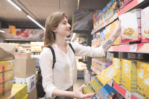 Carta da parati Happy young woman chooses flakes in a supermarket and smiles