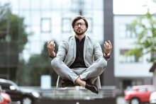 Attractive Young Businessman Floating In Air In Lotus Pose And Meditating At Parking